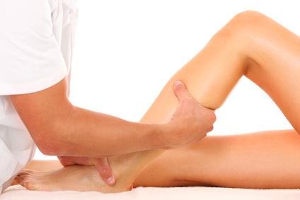 Therapeut massiert ein Bein