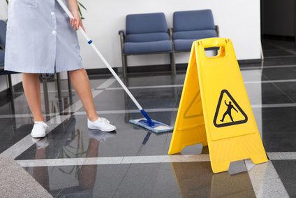 Reinigungskraft wischt eine Bodenfläche